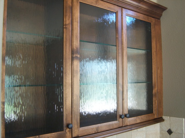 stained wood kitchen cabinets with rain glass doors and glass shelves