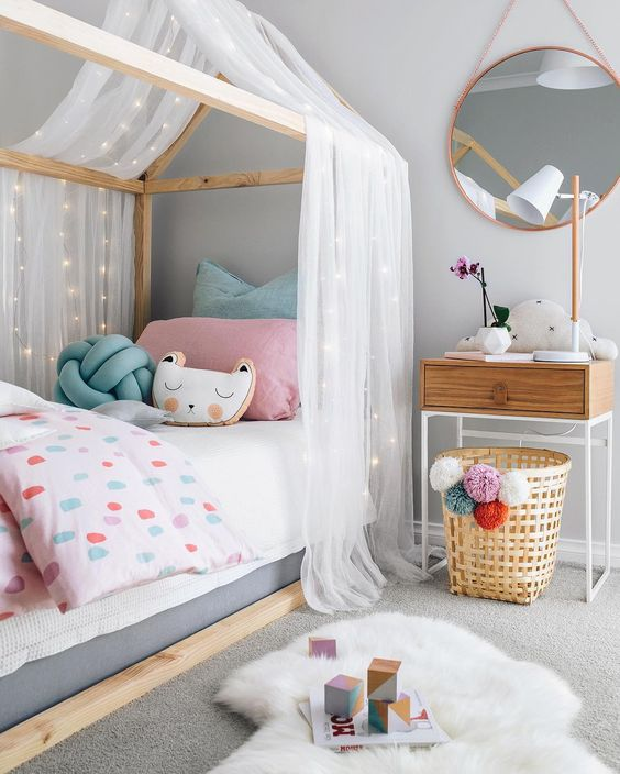 frame house bed with a tulle and lights canopy for some privacy