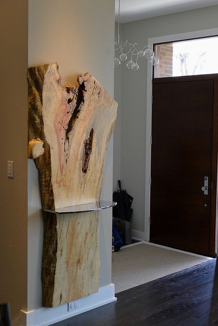 raw edge wood piece with a shelf attached for an entryway