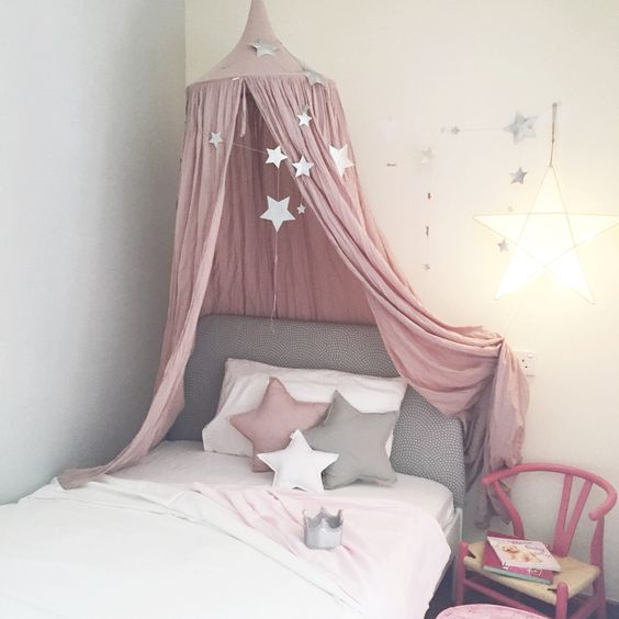 a grey bed with a pink star canopy and star garlands all over
