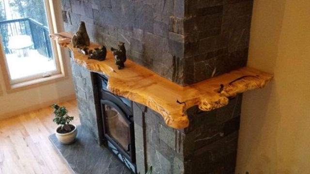 a fireplace with a raw edge wooden shelf all around