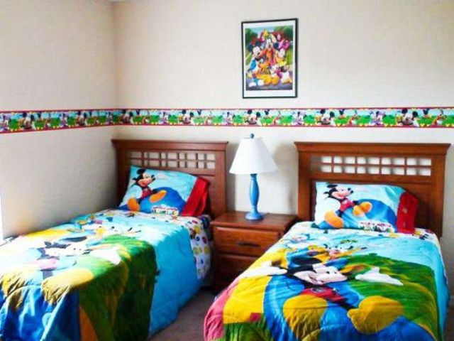 New colorful shared bedroom with bold bedding and wall decor
