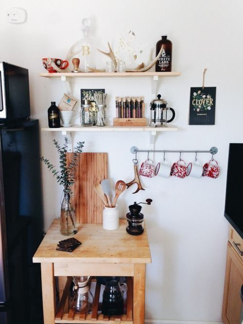 small drink station with hanging mugs, a tine table and a couple of shelves