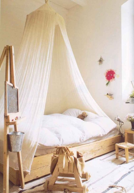 natural girl's room decor and a white tulle canopy that easily matches any design
