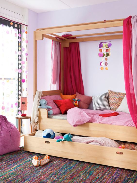 a wooden bed with colorful textiles and bold pink drapes