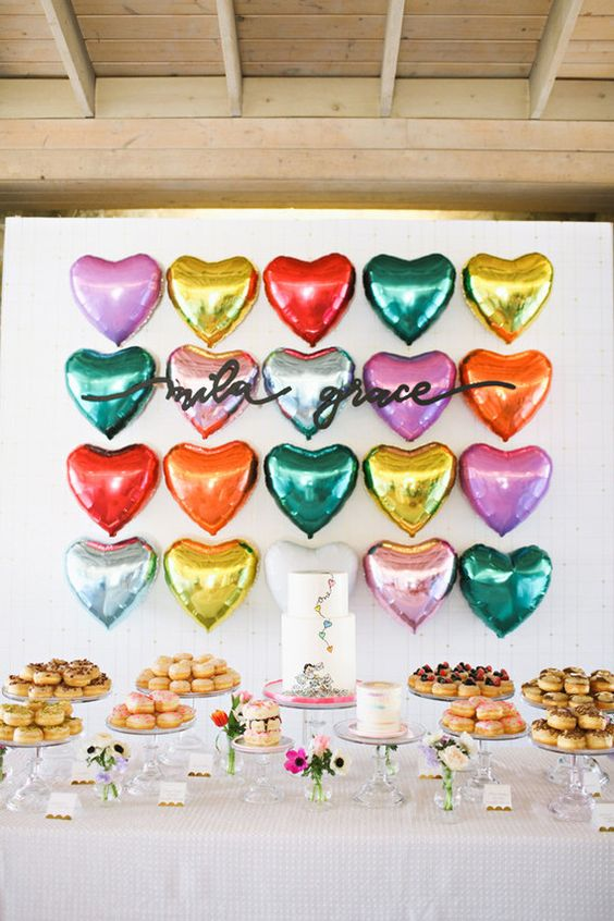 colorful heart balloons as a backdrop for the dessert table