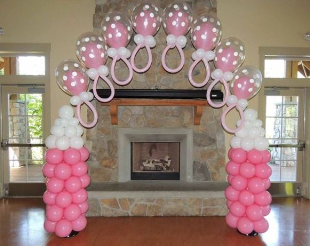 pink and white bottles and baby dummy balloon decorations for a girl's baby shower