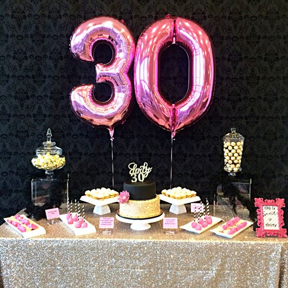pink number balloons, a glitter tablecloth and glam desserts