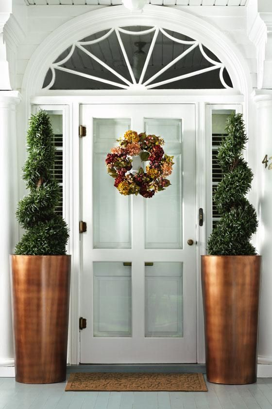 simple door with tall copper planters for a bold statement