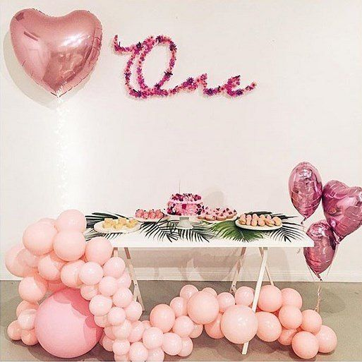 a pink balloon garland under the table