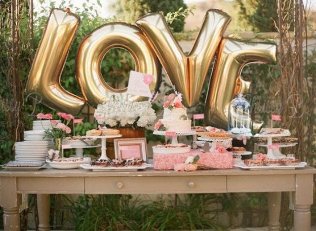 giant gold LOVE letter balloons may be used as a backdrop