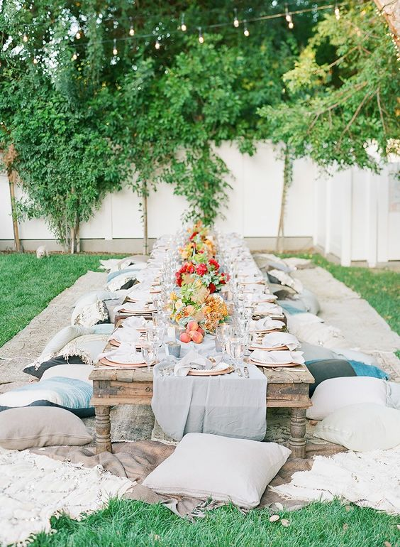 outdoor boho chic birthday party decor, a low table and pillows