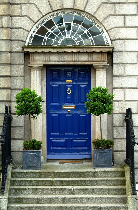 bold blue door and trees with shrubs in planters