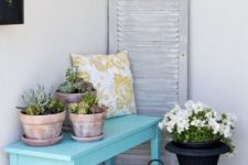 09 a blue bench with potted succulents, a yellow printed pillow and an urn with flowers