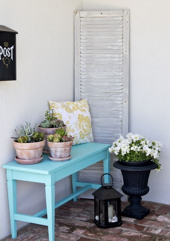 a blue bench with potted succulents, a yellow printed pillow and an urn with flowers