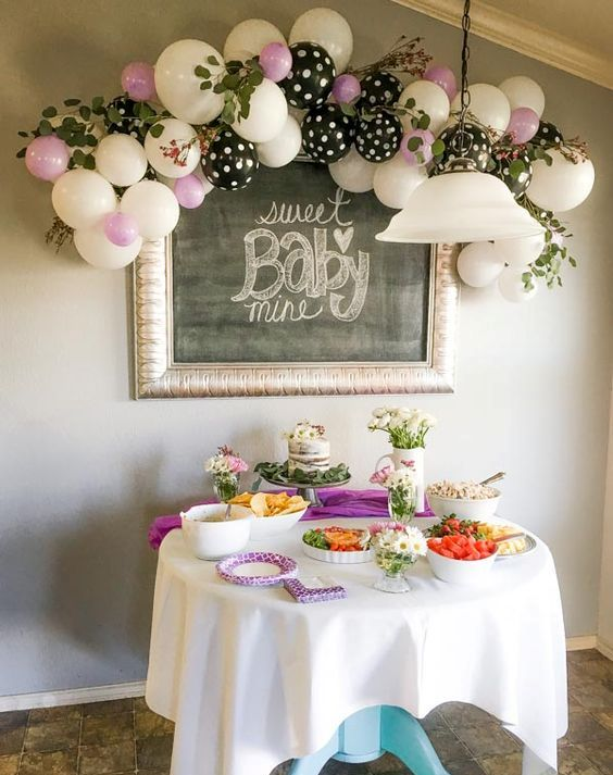 white, pink and polka dot balloon decoration over the dessert table
