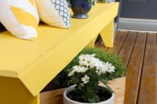 10 a bold sunny yellow bench and some plantered greenery and flowers