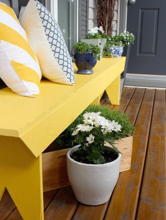a bold sunny yellow bench and some plantered greenery and flowers