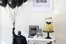 11 black balloons held by Batman for a boys' party