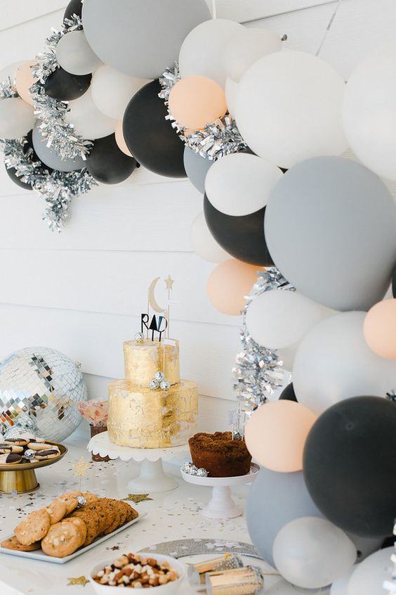cool modern balloon arch over the dessert table