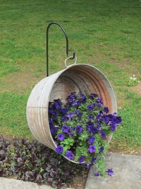 suspended old metal bathtub as a raised garden bed for a rustic look