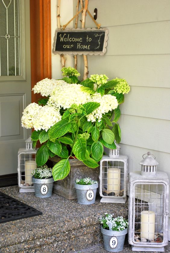 candle lanterns, planters with flowers and a large urn with lush greenery
