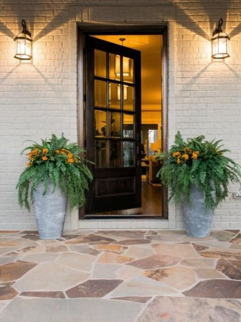 black glazed door and concrtee planters with fern and flowers