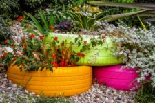 16 colorful tyre garden beds with various plants stacked on each other