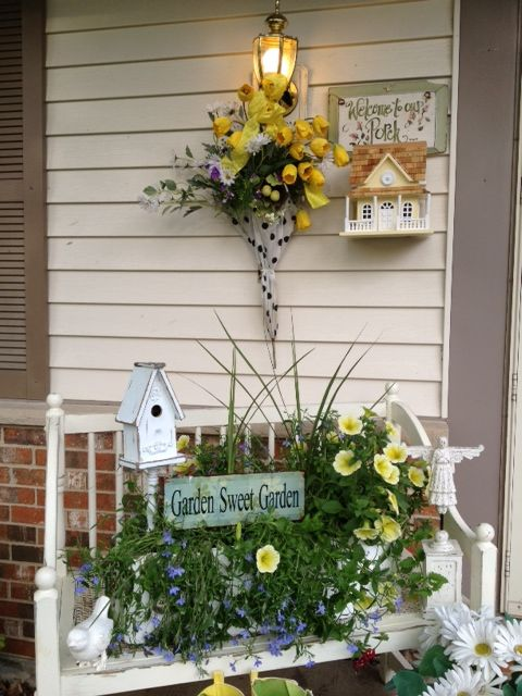 create a small garden on a porch bench putting some flowers and accessories there