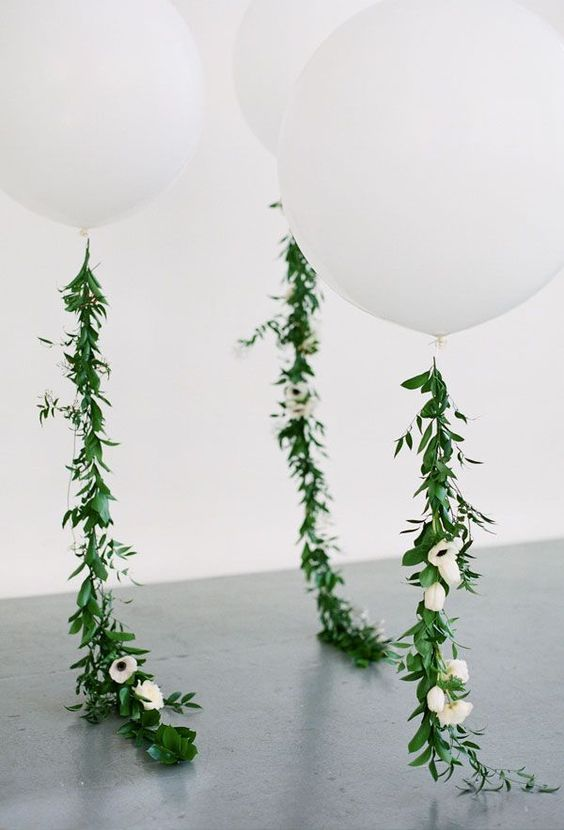 giant white balloons with greenery and flowers