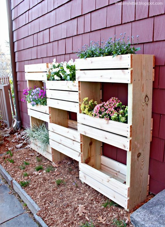vertical planter built of various crates and pallets to accomodate a lot fo greenery and flowers