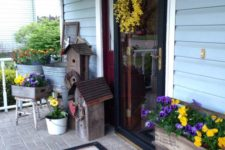 18 lots of bold flowers in various rustic planters to bring the spring feel to the porch