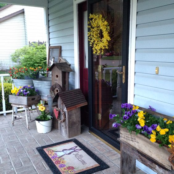 lots of bold flowers in various rustic planters to bring the spring feel to the porch