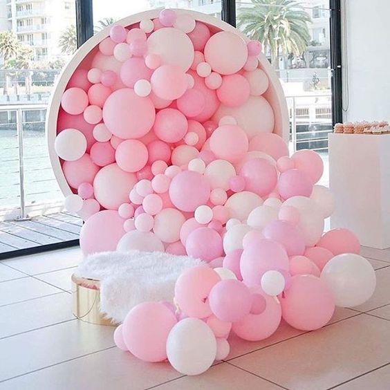 pink and white balloons falling from a large cup