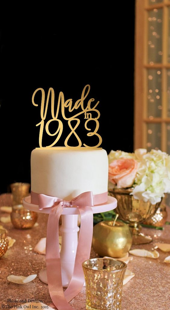 glam 30th birthday cake with pink ribbon and a gilded topper