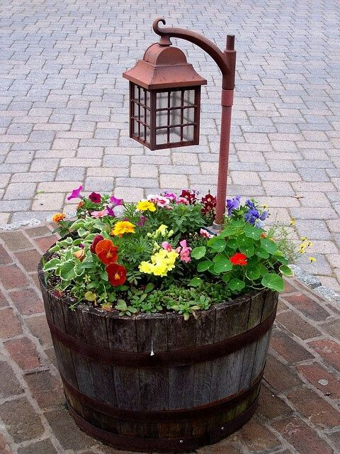 an old barrel turned intoa  garden bed with a light