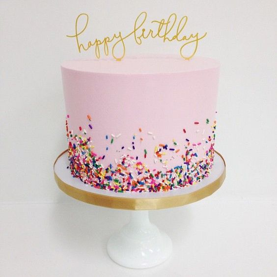 pink, sprinkles and a gold cake topper