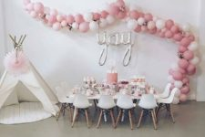 21 white and pink balloon garland over the reception