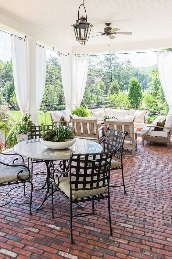 brick floor porch with an outdoor living room and gauzy curtains