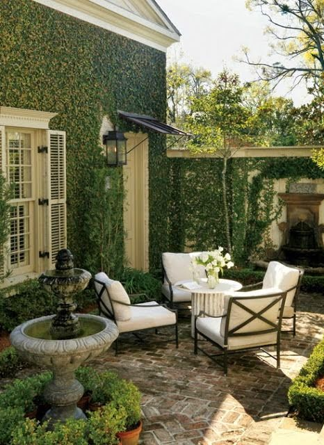 brick patio with a bird bath and lots of greenery around