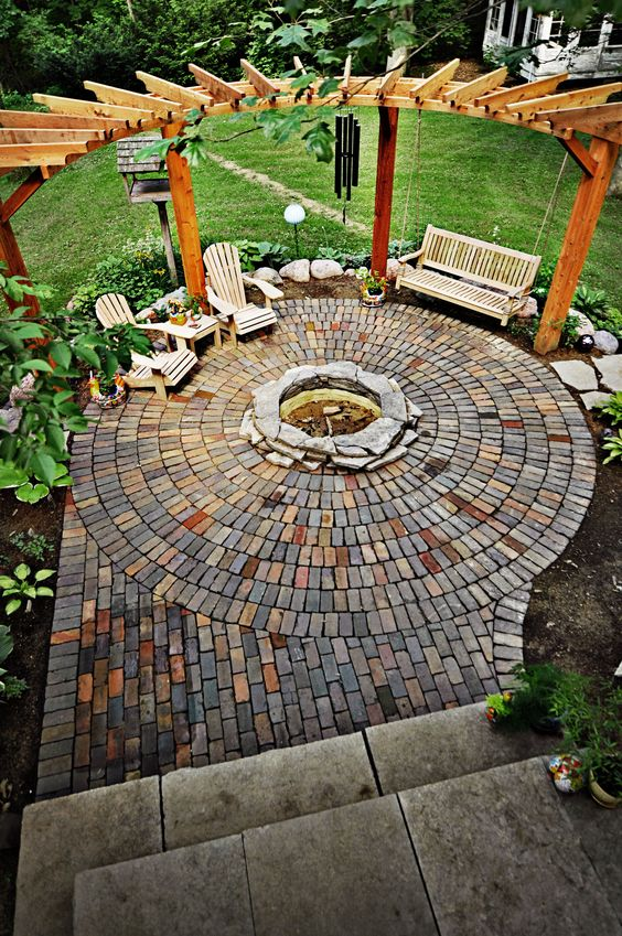 circle-clad brick patio with a fire pit and a swinging day bed