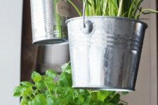 galvanized buckets and cans hung on a porch for a simple herb garden
