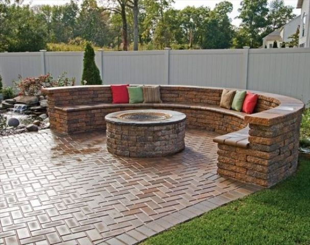 Delightful Herringbone Clad Brick Patio With A Fire Pit And A Round Bench Of Brick