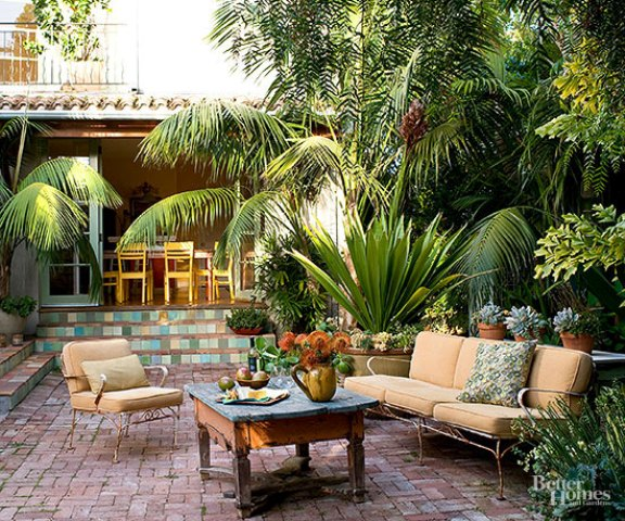 reclaimed bricks in various sizes bring been-around-awhile appeal to an antique-furnished patio positioned amid tropical foliage