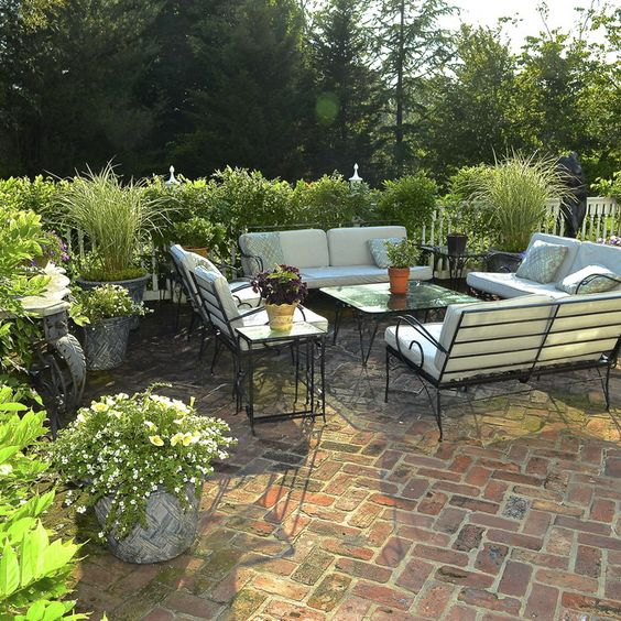 traditional patio decor with lots of greenery and herringbone clad brick