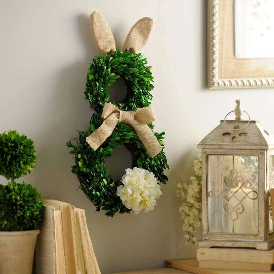 a boxwood bunny wreath with burlap ears and a bow and a fluffy tail