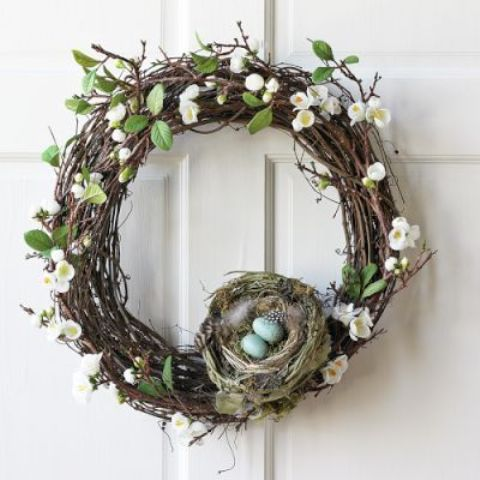a grapevine wreath with faux spring blooms, leaves and a nest
