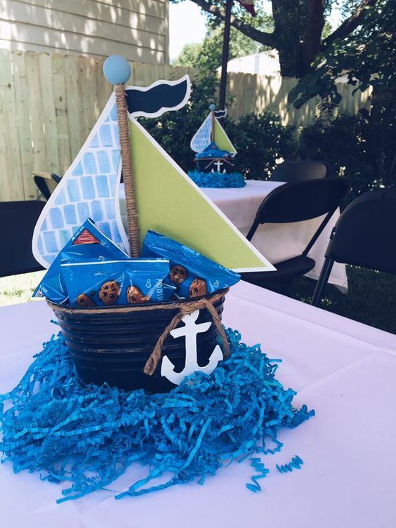 a nautical centerpiece of a bucket with crackers and an anchor