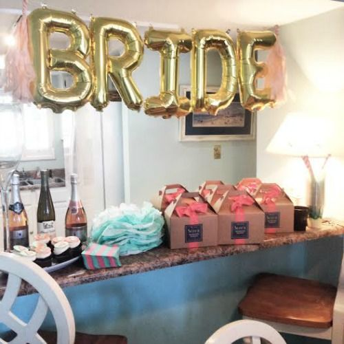 favor table with gold balloon BRIDE letters garland over it