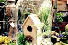 03 a cloche with a bird house, eggs and some greenery is perfect for spring